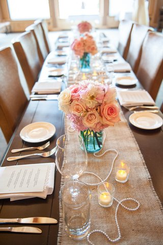 burlap-table-runner-with-pink-and-white-roses-in-blue-mason-jar-and-pearls