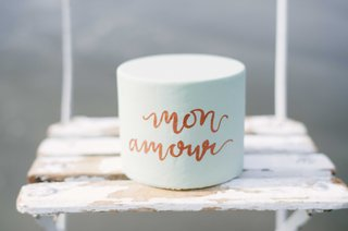 small-light-blue-cake-with-rose-gold-calligraphy-saying-mon-amour-on-a-wooden-chair