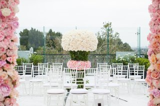 white-ceremony-seating-on-rooftop-white-flower-pink-rose-arrangement-in-between-seats