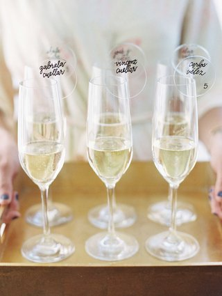 champagne-flutes-filled-with-bubbly-and-lucite-acrylic-circles-with-calligraphy-and-table-numbers