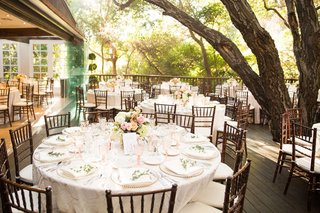 wedding-reception-outdoor-tables-light-color-palette-low-centerpieces-roses-wood-chairs-greenery