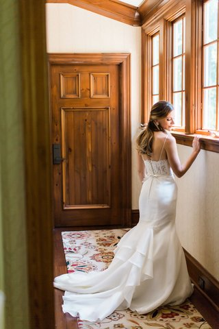 bride-in-rustic-wedding-venue-with-lace-back-corset-wedding-gown-and-sleek-skirt-spaghetti-straps