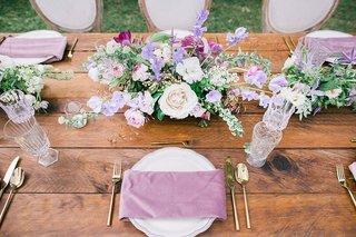 wedding-reception-rustic-wood-table-purple-napkin-gold-flatware-greenery-white-purple-centerpiece
