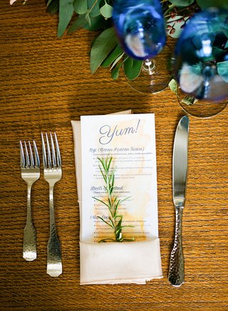 wood-table-at-wedding-reception-royal-blue-glassware-sprig-of-herb-rosemary-in-napkin-watercolor-yum