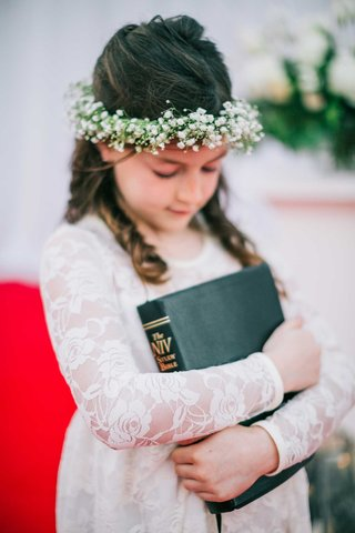 flower-girl-in-lace-long-sleeve-dress-with-babys-breath-flower-crown-hugging-bible-holiday-wedding