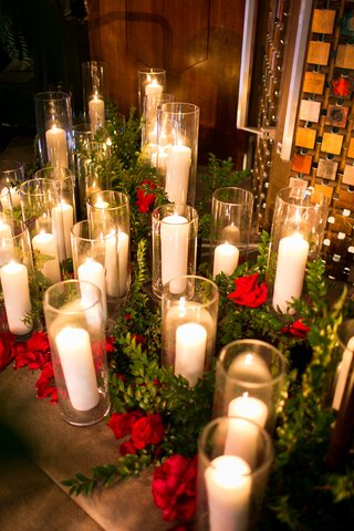 red-flowers-and-greenery-around-candles-in-hurricane-vases-on-floor-of-temple-jewish-wedding