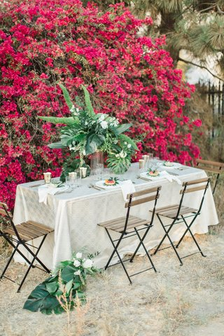 rustic-chic-styled-shoot-table-champagne-linen-deck-chairs-foliage-bougainvillea-wall