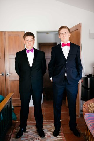 grooms-standing-wearing-black-suits-and-purple-and-red-bow-ties-double-wedding