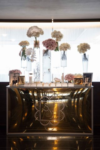 mirror-escort-card-table-with-tall-glass-vases-topped-with-bouquets-of-white-and-pink-flowers-frames