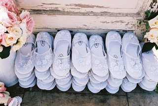 white-slippers-for-guests-to-wear-on-sand-at-beach-wedding