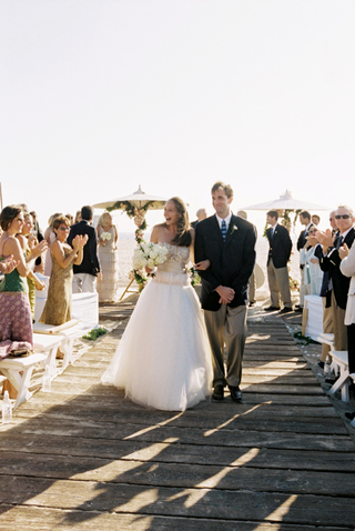 bride-and-groom-walk-up-wood-plank-aisle-on-beach