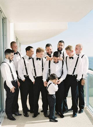 groom-and-groomsmen-on-balcony-with-ring-bearer-all-in-tuxedo-pants-suspenders-and-bow-ties