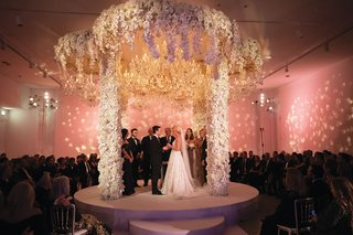 wedding ceremony opulent design orchid flowers grand chandelier circular stage chuppah