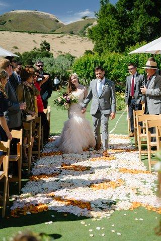 bride-in-blush-ruffled-mermaid-dress-walks-down-the-aisle-with-groom-in-grey-suit-and-sky-blue-tie