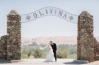 bride-in-hayley-paige-dress-kisses-groom-at-olivina-stone-gate
