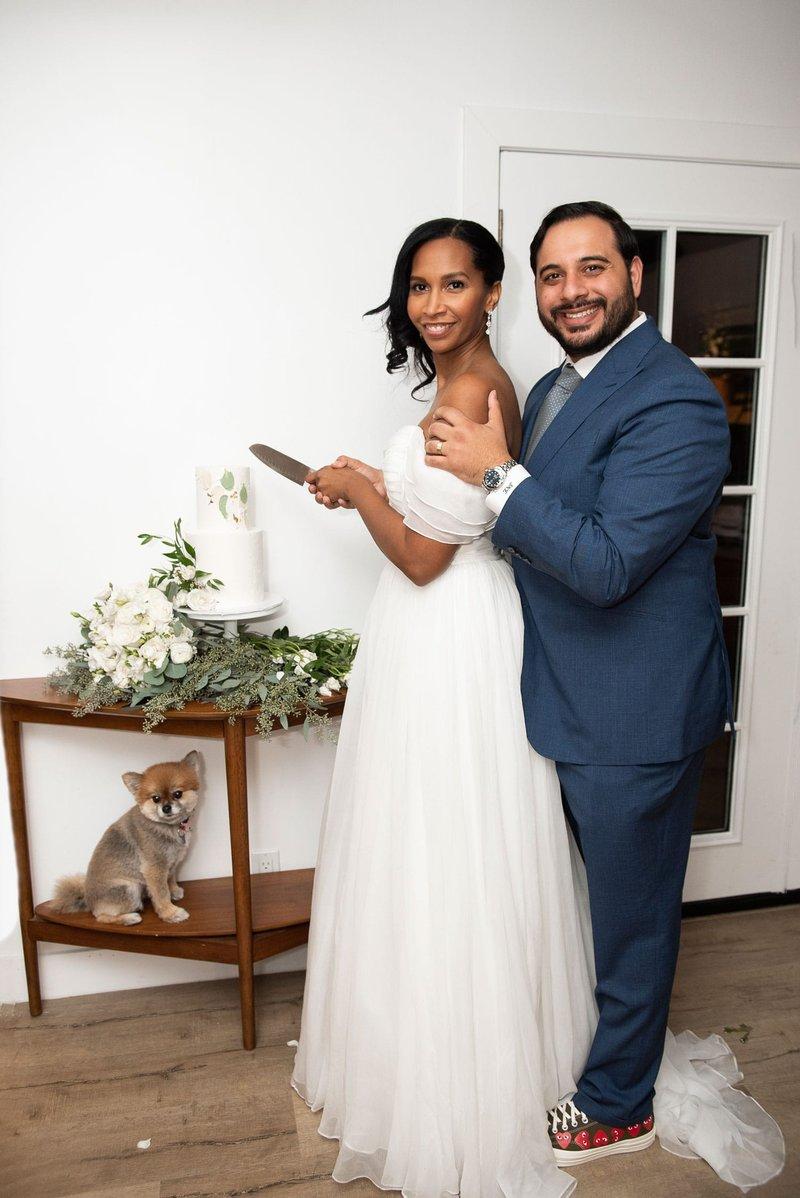 Couple Cutting Wedding Cake with Dog