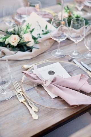 wooden-table-with-gold-rimmed-clear-charger-blush-napkin-gold-flatware