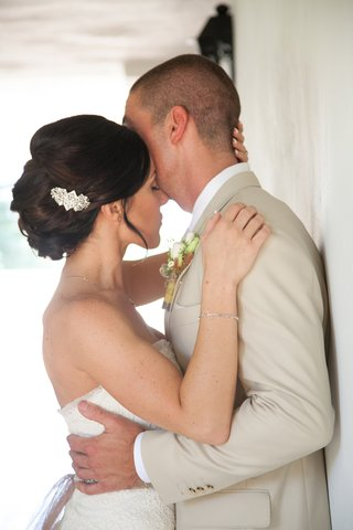 bride-embraces-groom-with-pretty-wedding-hair-updo-and-jewel-clip