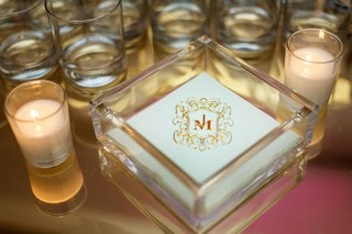 wedding-reception-beverage-napkin-with-monogram-surrounded-by-candles