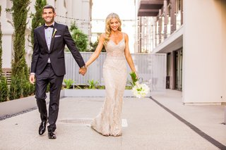 bride-in-berta-bridal-gown-and-jewel-headpiece-holds-hands-with-groom-in-tuxedo