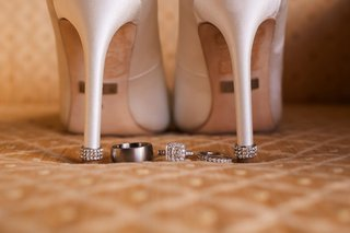 wedding-detail-shot-white-bridal-heels-shoes-jewel-heel-platinum-wedding-band-halo-engagement-ring