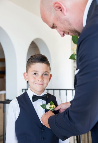 wedding-ceremony-ring-bearer-with-vest-and-bow-tie-boutonniere-being-put-on-by-groom-new-step-dad