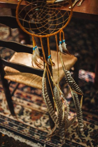 wedding-reception-chair-with-tan-dreamcatcher-with-blue-beads-brown-and-white-feathers