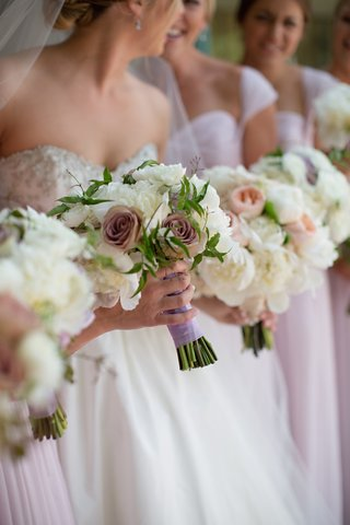 bridesmaid-bouquet-of-white-peonies-purple-roses-and-greenery-hand-tied-in-light-purple-ribbon