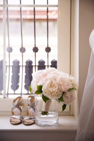 pretty-bridal-bouquet-in-glass-vase-next-to-silver-shoes-on-windowsill