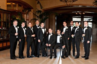 groom-and-groomsmen-wearing-black-suits-with-black-bow-ties-and-silk-accents