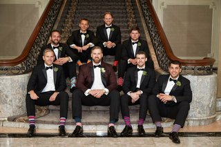 groom-in-burgundy-tuxedo-jacket-with-groomsmen-in-tuxedos-with-funny-fashionable-socks