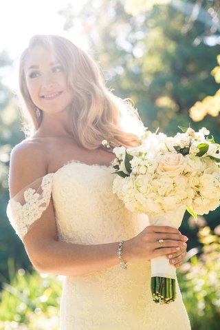 bride-holding-white-bouquet-rose-hydrangea-greenery-off-shoulder-lace-wedding-dress-anne-barge