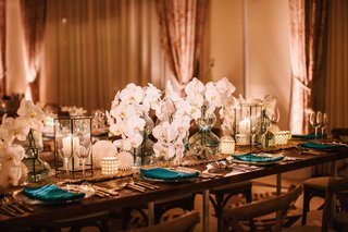 wedding-reception-table-wood-with-table-runner-blue-vases-white-orchid-flowers-in-center
