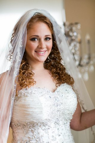 bride-in-sweetheart-neckline-wedding-dress-with-curly-red-hair-and-embroidered-veil