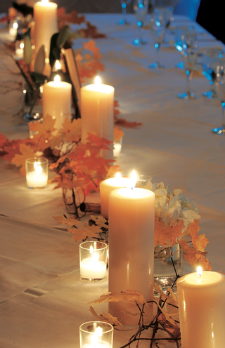 white-pillar-candles-and-autumn-leaves-on-guest-table
