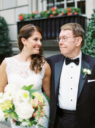 bride-in-white-lace-wedding-dress-and-bouquet-smiles-at-father-of-bride-in-tuxedo-with-bow-tie