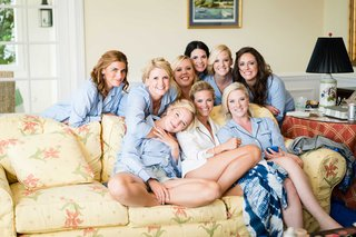bride-on-yellow-couch-with-bridesmaids-in-light-blue-pajamas-mens-button-down-shirts