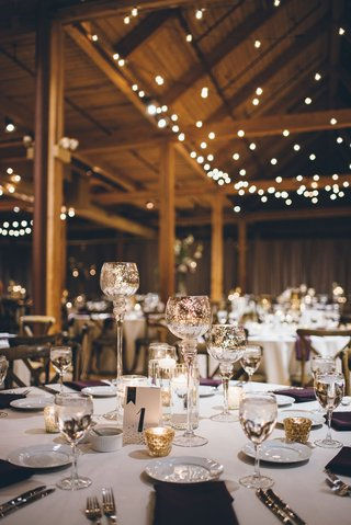 wedding-reception-with-confetti-table-number-gold-candleholders-and-wine-glasses-and-twinkle-lights