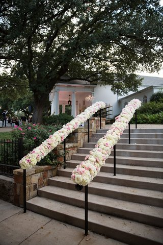 white-and-pink-rose-flowers-on-hand-rail-going-up-stairs-at-outdoor-wedding-venue