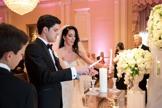 bride-and-groom-lighting-candle-during-unity-candle-ceremony-at-dallas-wedding