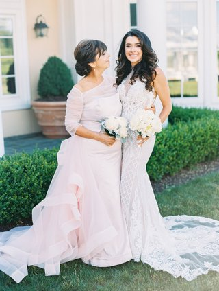 bride-with-curled-hair-form-fitting-sleeveless-wedding-dress-with-mother-in-pink-gown-sleeves