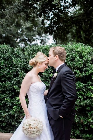 groom-kissing-bride-forehead-classic-wedding-strapless-dress-tuxedo-simple-white-bouquet-dallas-tx