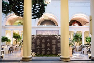 museum-wedding-reception-the-field-museum-tall-columns-and-black-white-seating-chart-greenery-decor