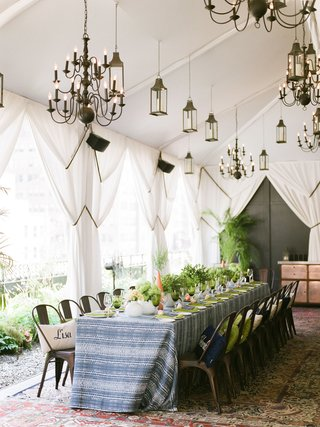 bridal-shower-moroccan-rugs-blue-white-linens-industrial-chairs-place-card-pillows-lanterns-drapery