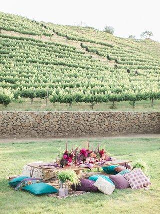 reception-table-pillow-seats-bold-color-scheme-california-boho-chic-wedding-styled-shoot-vineyard