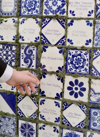 wedding-reception-guest-grabbing-cocktail-hour-escort-card-blue-white-hand-painted-tile-greenery