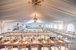 wedding-reception-space-farm-tables-gold-chiavari-chairs-white-drapery-ceiling-floral-chandeliers