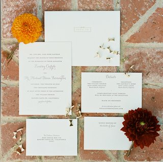 simple-white-wedding-invitations-with-wedding-information-and-gold-bow-pins