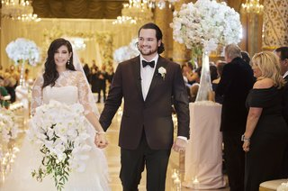 bride-in-vera-wang-ball-gown-and-full-orchid-bouquet-holding-hands-during-recessional-with-groom