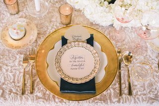 wedding-reception-place-setting-with-golden-charger-gold-rimmed-and-patterned-china-golden-flatwar